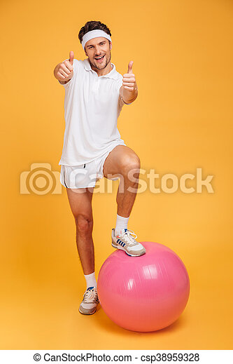 Sportsman with one foot on fitness ball showing thumbs up - csp38959328