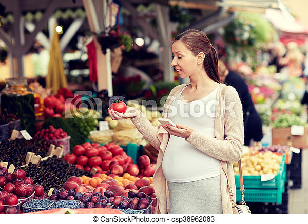 sale, shopping, food, pregnancy and people concept - happy pregnant woman with smartphone choosing vegetables at street market