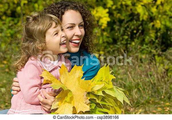 young woman and little girl laugh with leaves in hands in garden autumn