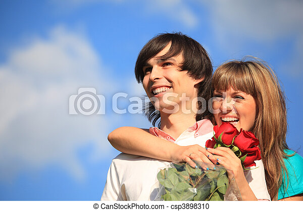girl with bouquet of roses embraces behind guy against sky - csp3898310
