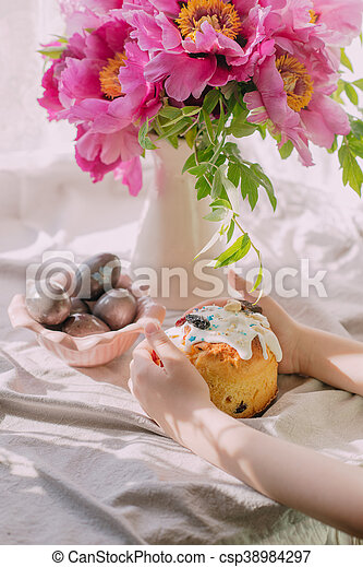 on the windowsill bunch of decorative pink peonies in a vase and cake with Easter eggs