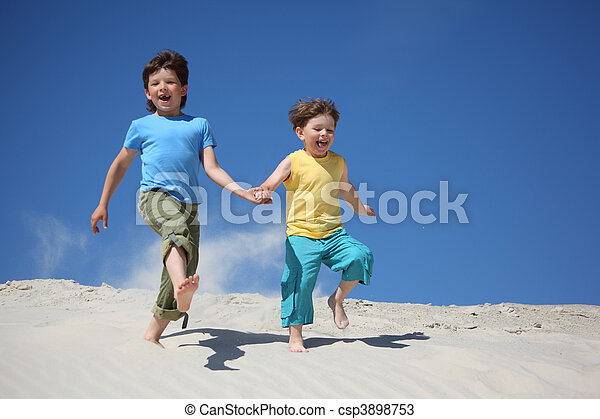Two boys run on sand - csp3898753