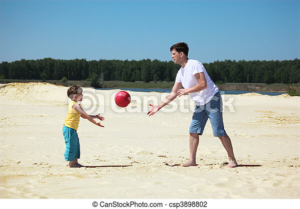 father and son throw each other ball on sand - csp3898802