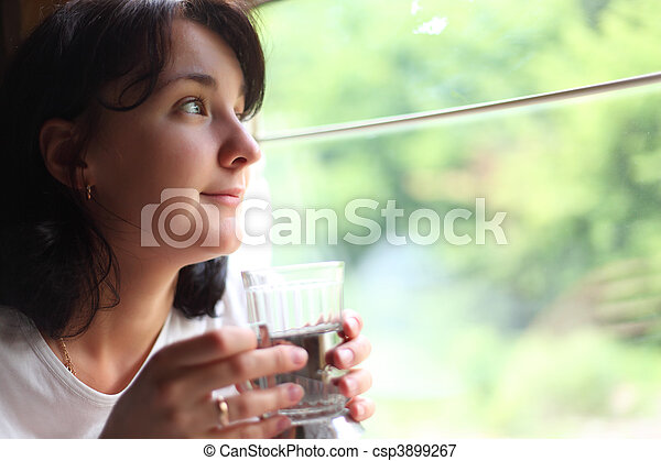 young woman holds glass andlooks in train`s window - csp3899267
