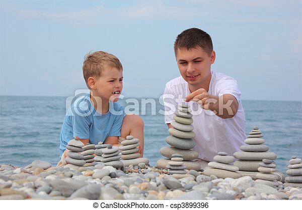 stock image of father and son builds stone stacks on pebble beach csp3899396 search stock. Black Bedroom Furniture Sets. Home Design Ideas