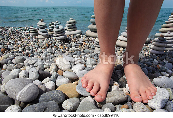 two legs and stone stacks on pebble beach - csp3899410