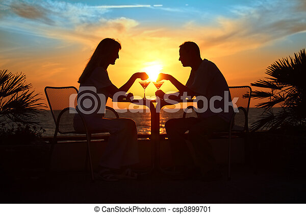 Female and man\'s silhouettes on sunset sit at table with two gla - csp3899701