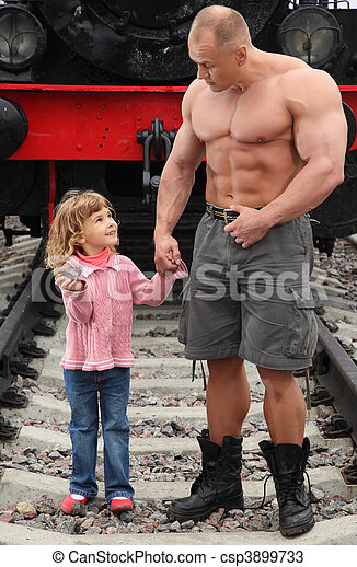strong shirtless man stands on railroad with little girl - csp3899733