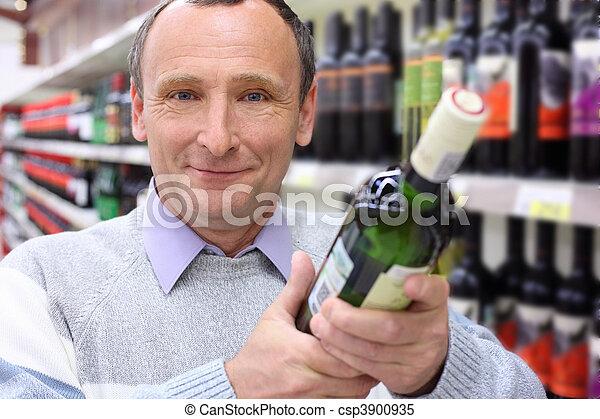 happy elderly man in shop with wine bottle in hands - csp3900935