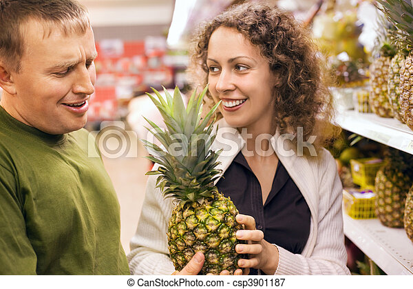 Smiling young man and woman buy pineapple in supermarket - csp3901187