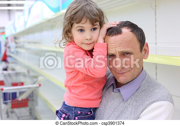 elderly man at empty shelves in  shop with child on hands - csp3901374