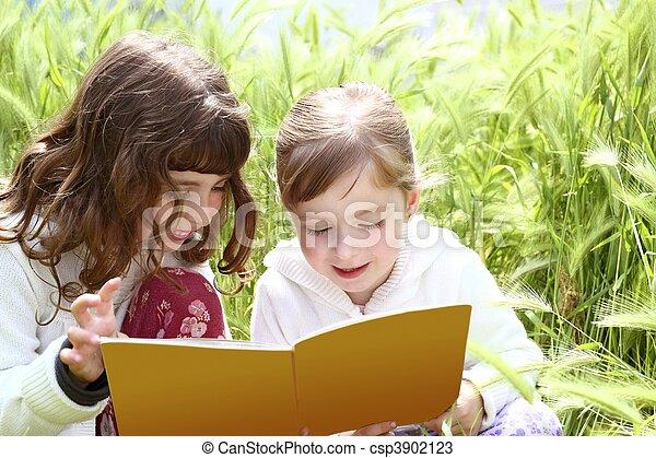 tow little sister girls reading book spikes garden - csp3902123