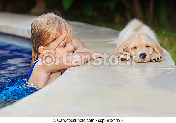 Funny photo of little baby swimming in blue outdoor pool look at lazy retriever puppy. Children water sports activity and swimming lessons, training dogs, fun games with family pet on summer vacation.