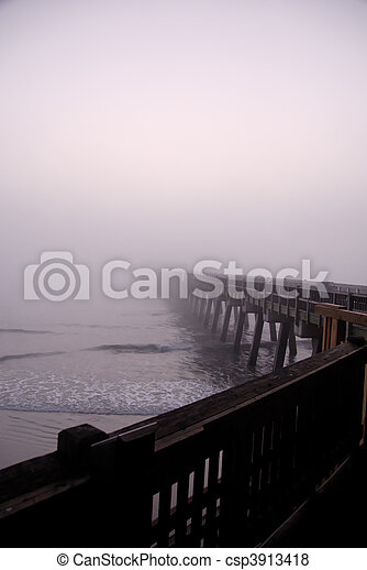 A pier disappearing into the fog at the ocean.