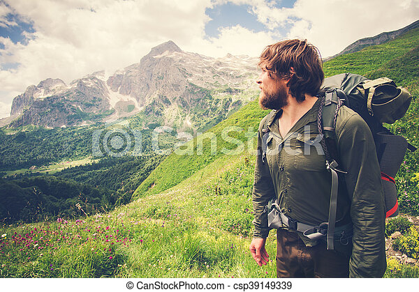 Young Bearded Man Traveler with backpack mountaineering Travel Lifestyle concept mountains on background Summer adventure vacations outdoor