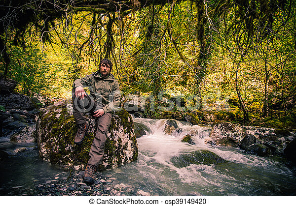 Young Man bearded relaxing hiking outdoor with river and forest wild on background Lifestyle Travel survival concept