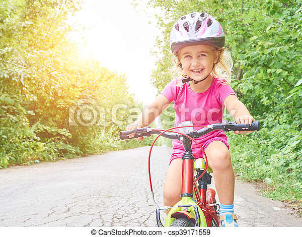 Happy child riding a bike in outdoor. Cute kid in safety helmet biking outdoors. Little girl on a red bicycle Healthy preschool children summer activity.