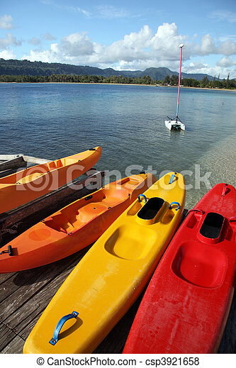 Tropical holiday scene in Vanuatu in the South Pacific. Colourful sea kayaks and sailing boat in the background. - csp3921658