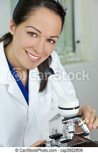 A beautiful female medical or scientific researcher using her microscope in a laboratory. - csp3922806