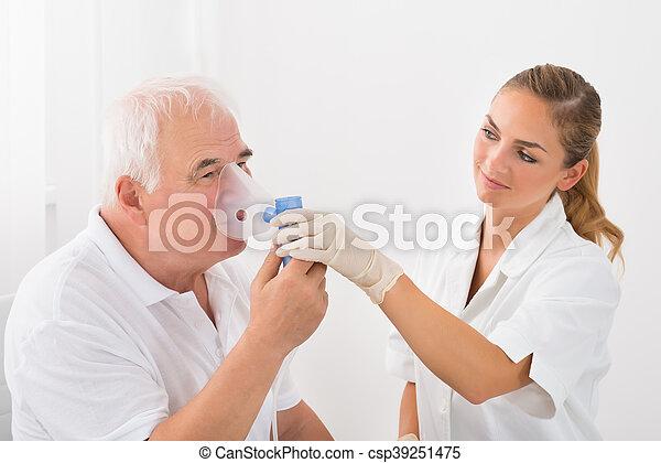 Patient Inhaling Through Oxygen Mask - csp39251475