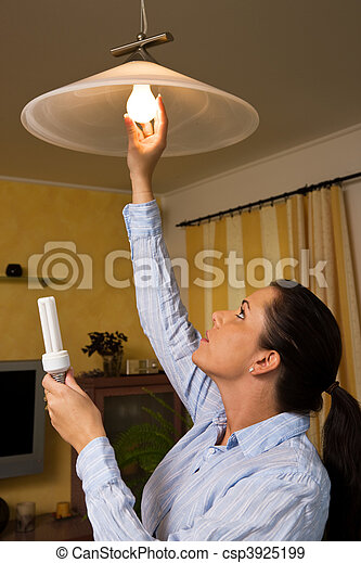 Young woman changes in energy-saving light bulb lamp - csp3925199
