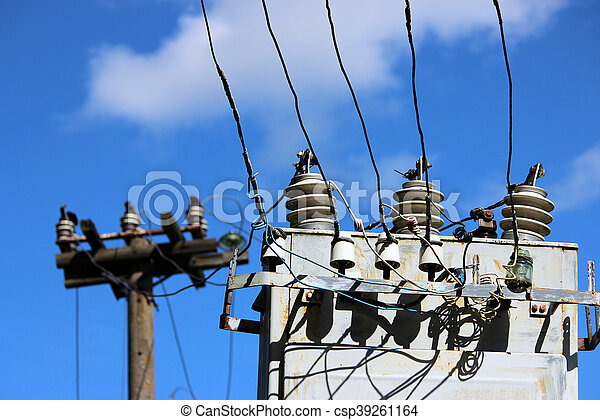 electrical wires extending from the transformer station near the railway on a background of blue sky