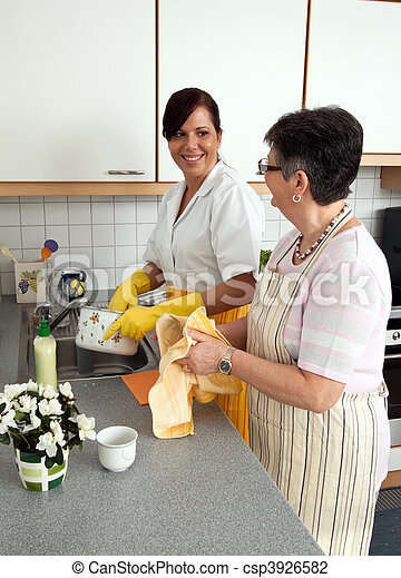 Nurse with a senior citizen with the dishes - csp3926582