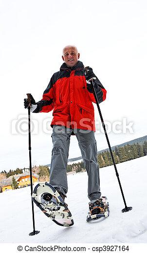 Senior at the snow-shoe walking in winter - csp3927164