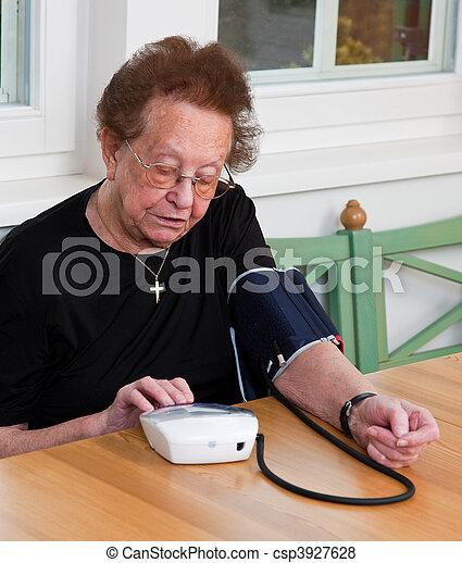 Senior citizen measure blood pressure - csp3927628
