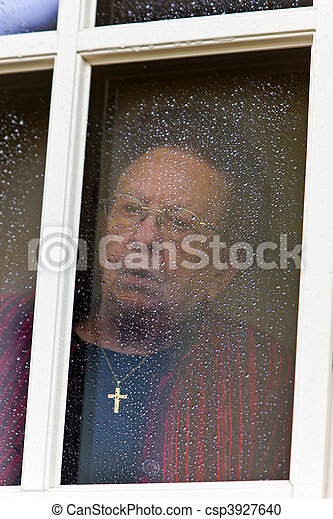 pensive looks sad senior citizen out of a window - csp3927640