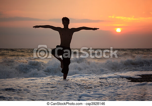 Silhouette guy yoga on sunset wavy beach - csp3928146