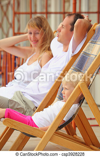 Happy family with little girl reclining on chaise lounges on veranda - csp3928228