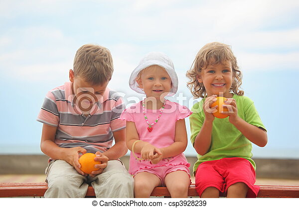 boys and girl with oranges and one liittle girl with panama hat is sitting on wooden bench. boy wearing stripped t-shirt looking at orange. focus on face of girl with orange.