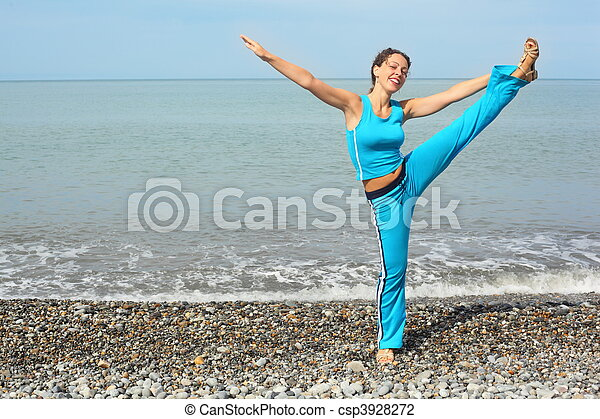 joyful woman wearing sporty clothers stretching on sea coast - csp3928272