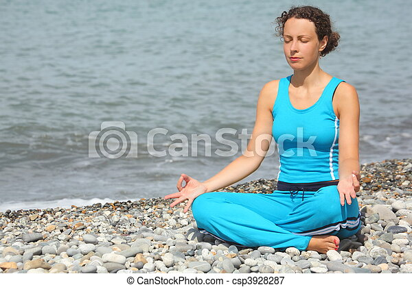 joyful woman wearing sporty clothers is meditate on a sea coast. - csp3928287