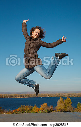 ?heerful girl in jump against dark blue sky. Productive leisure leads to success. - csp3928516