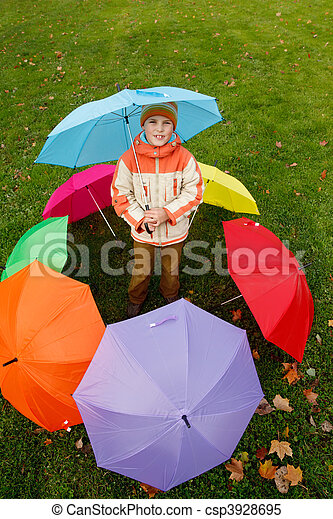Boy in autumn park, in environment of multi-coloured umbrellas. Top view. - csp3928695