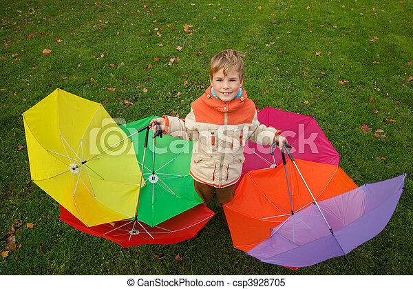 Boy in autumn park, in environment of multi-coloured umbrellas. Top view. Horizontal format. - csp3928705