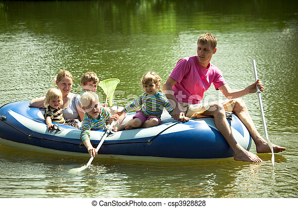 Children and adults float on an inflatable boat and fish a net. - csp3928828