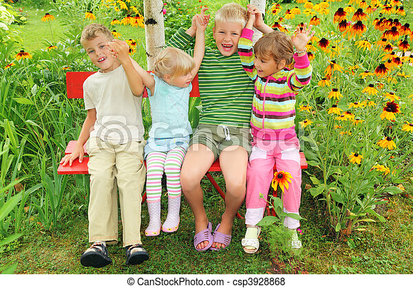 Children sitting on bench in garden, having joined hands - csp3928868