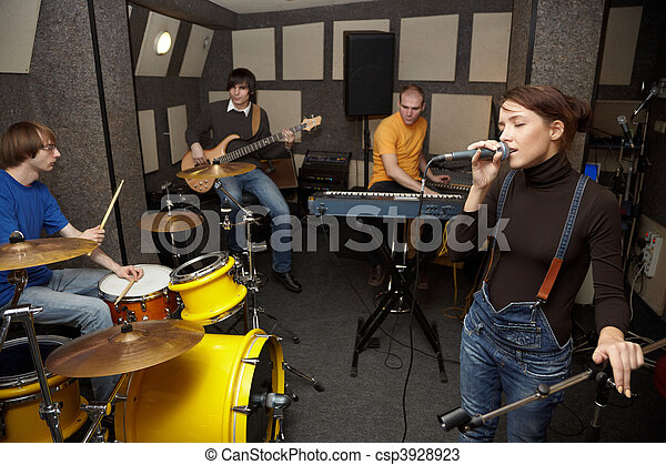 a rock band working in studio. vocalist girl is singing. focus on clothers of vocalist girl - csp3928923