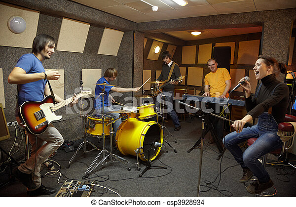 a rock band. vocalist girl, two musicians with electro guitars, keyboarder and one drummer working in studio. the joy of creation