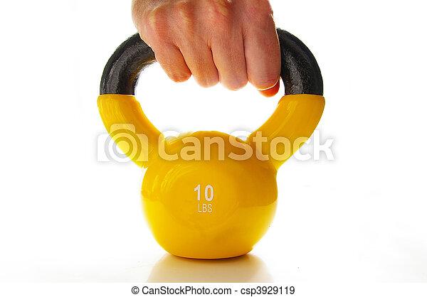 man grabbing a ten pound kettle-bell weight - csp3929119