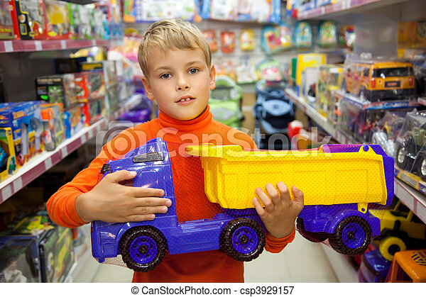 The boy in shop with toy truck in hands - csp3929157