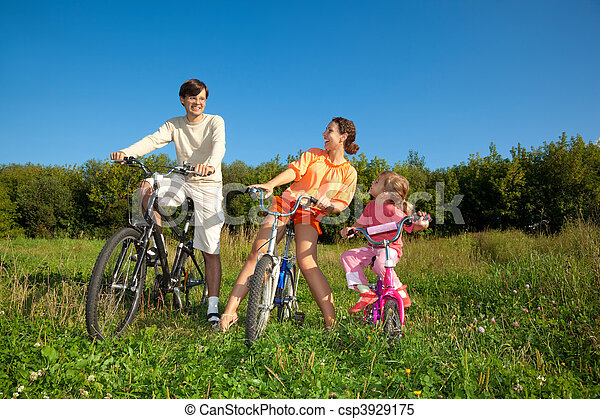 Family from three persons on bicycles in the country. Mum with a daughter look at the daddy. - csp3929175