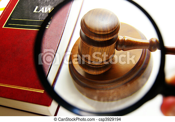 magnifying glass examining a judges court gavel, with law book - csp3929194