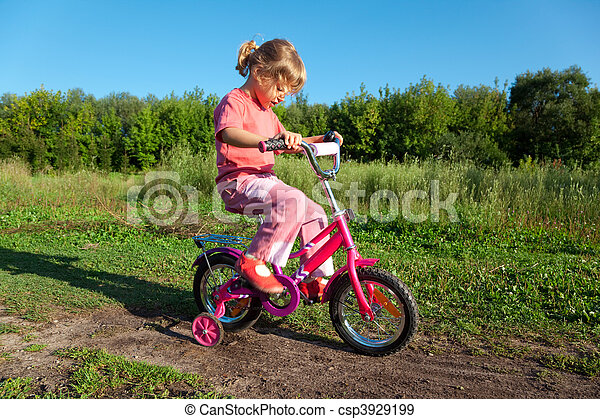 The little girl goes for a drive on a pink bicycle in park - csp3929199