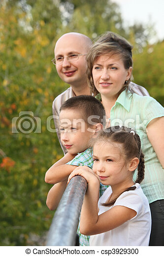 dad, mom, little boy and girl is lean elbow on bridge fence and looking away - csp3929300