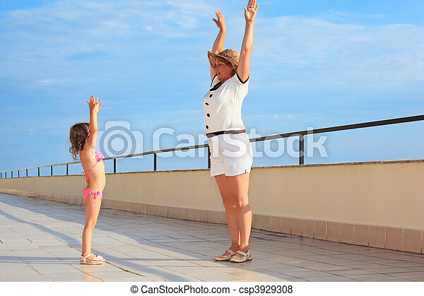 elderly woman and  little girl do morning exercise on veranda near seacoast, lifted hands upwards - csp3929308
