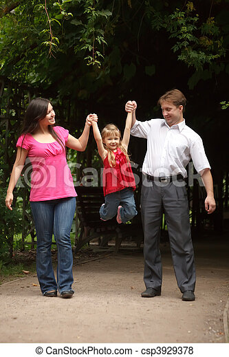 Little girl in red dress with father and mother in park. Girl plays being shaken on hands of parents. - csp3929378